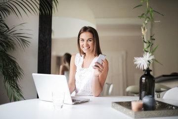 Smiling woman using a smartphone and a laptop