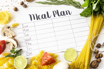 A meal plan for a week on a white table among products for cooking - pastas, basil, vegetables, lime, seeds, nuts and spices. Top view, flat lay, copyspace Wall mural