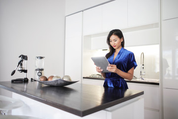 Woman standing in the kitchen using a tablet