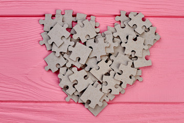 Shape of heart from cardboard puzzles. Grey jigsaw puzzles forming shape of heart on colorful wooden background.