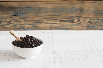 Coffee beans in white ceramic bowl on table
