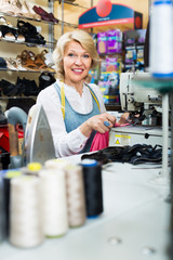 friendly middle-aged woman tailor using sewing machine