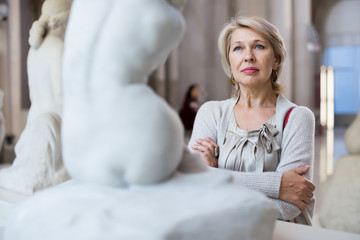 woman visitor near sculpture in the museum