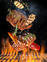 Aluminium Prints Grill / Barbecue Tasty beef steaks flying above cast iron grate with fire flames.