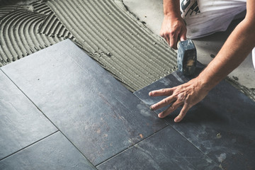 Worker placing ceramic floor tiles on adhesive surface, leveling with rubber hammer Fototapete