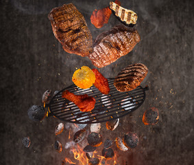 Hot briquettes, cast iron grate and tasty meats flying in the air.
