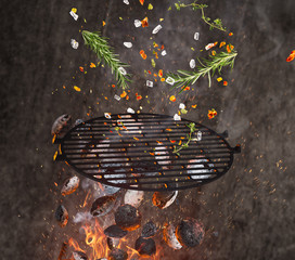 Hot briquettes, cost iron grid and spices flying in the air.