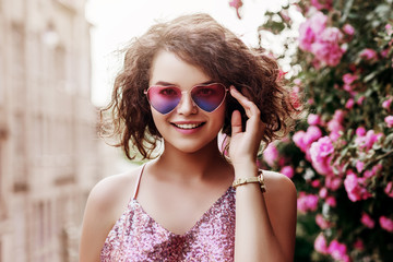 Outdoor close up portrait of young beautiful happy smiling curly girl wearing stylish heart gradient sunglasses, pink sequin blouse. Model posing near blooming roses. Summer fashion concept