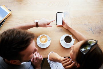 Fototapeta Mockup, friends browsing phone together at cafeteria obraz