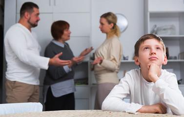 Unhappy boy during parents and grandma quarreling
