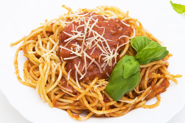spaguetis a la bolognese dish with cheese and basil leaf