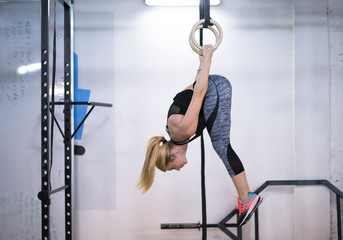 woman working out on gymnastic rings