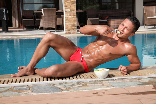 Muscular young sexy wet guy in a speedo eating fruit near the pool
