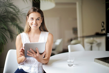 Smiling young woman holding a tablet