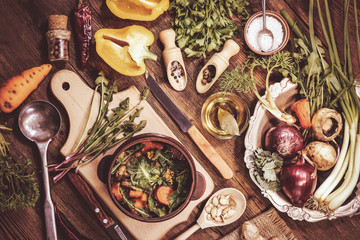 cooking of spring dish dandelions with pumpkin and mushrooms. ingredients and spices. wooden background.