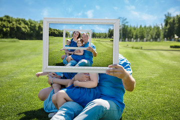 Smiling family with children looking through an empty frame
