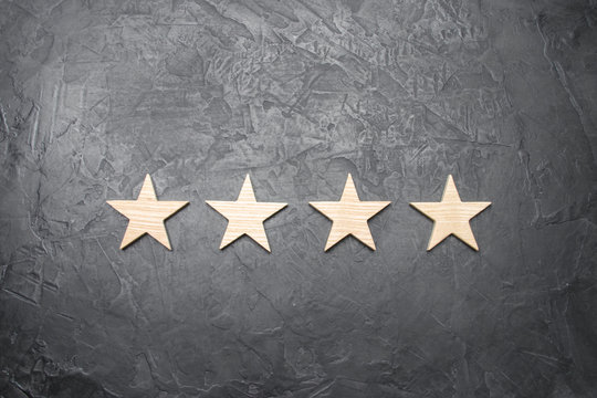 four stars on a dark background. The concept of rating and evaluation. The rating of the hotel, restaurant, mobile application. Quality service, buyer choice. Success in business
