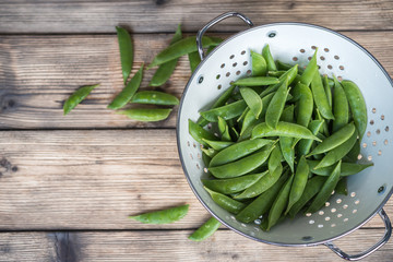 sugar snap peas in a white colander on a wooden table