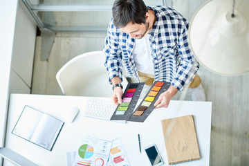 From above of young casual man at working desk choosing colors from bright palettes in light office.