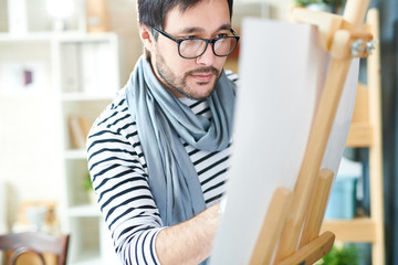 Trendy man working on illustration drawing with pencil on paper standing at easel.