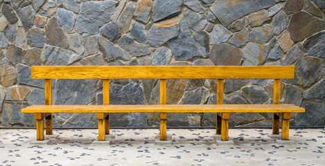 varnished wooden bench against a stone wall on a floor with a pebble design in a gazebo at a Japanese garden