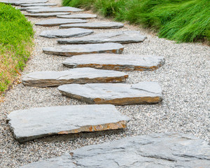 simple flat stone pathway on gravel surrounded by bright green grass in a Japanese garden