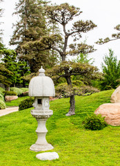 Nure Sagi carved lantern surrounded by lush greenery in a Japanese garden