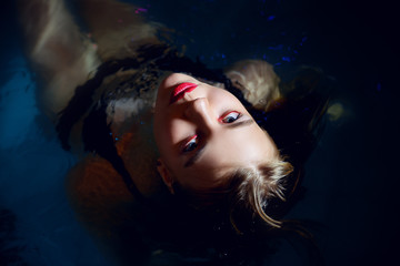 Glamorous young woman with brown make-up and clean skin in the pool close-up with her legs up.