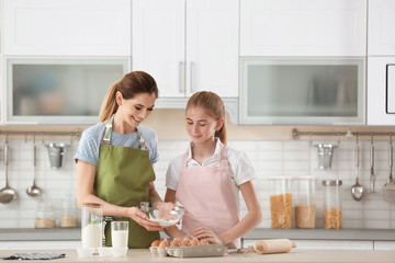 Mother and her daughter making dough at table in kitchen