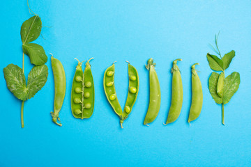 Fresh green ripe sugar snaps, sweet peas copy space close up on blue background, flat lay food concept