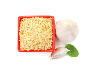 Bowl of granulated dry garlic and basil on white background, top view