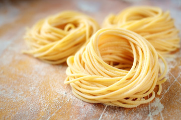 raw homemade spaghetti nest with flour on a wooden table. fresh Italian pasta Wall mural