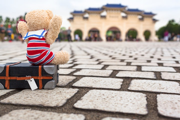 Cutie Happy to Travel in Taipei / Little teddy bear with nostalgic sailor suit sitting on suitcase, lift his arms up to say hooray in Taipei city, Taiwan