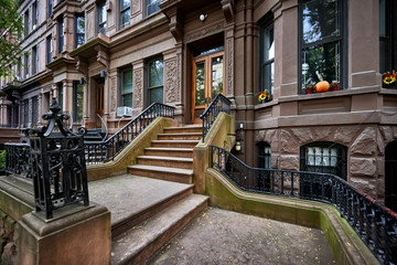 a row of brownstone buildings and stoops in an iconic neighborhood of Manhattan, New York City