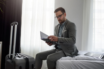 Traveling for work. Elegant businessman sitting in his hotel room working