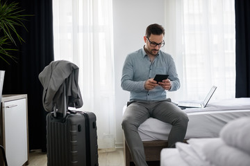 Businessman using smart phone at hotel room