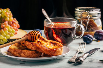 Healthy breakfast concept. French toasts with honey, fruits and tea over white wooden background