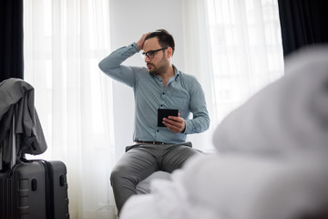 Exhausted businessman sitting on bed in hotel room