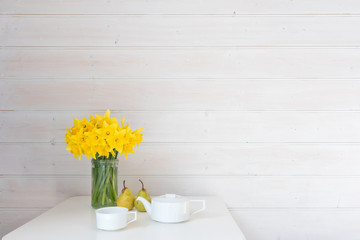 Yellow daffodils in glass jar on white table with two green pears and white teapot against rustic white wood panelled wall