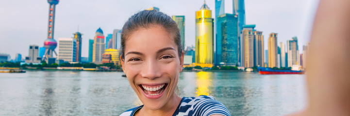 Wall Mural - China travel selfie Asian tourist woman talking happy panorama banner landscape. Smiling young girl taking picture with phone of herself in front of Shanghai's skyline of skycrapers.