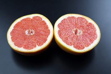 cut grapefruit on a dark background