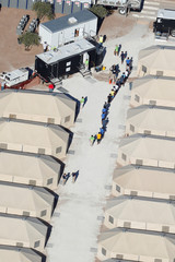 """Immigrant children now housed in a tent encampment under the new """"zero tolerance"""" policy by the Trump administration are shown walking in single file at the facility near the Mexican border in Tornillo, Texas"""