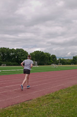 A young lady running  on a running track next to a soccer field and woods