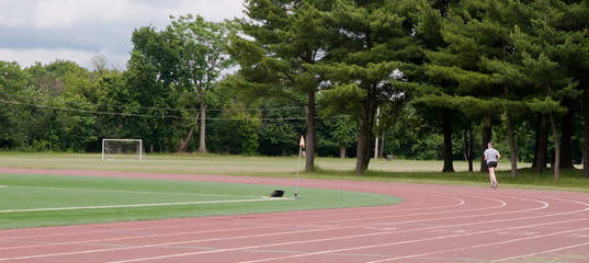A young lady running in the distance on a running track next to a soccer field and woods