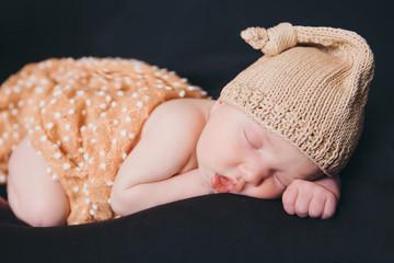 A little child in a beige cap lies on tje black background