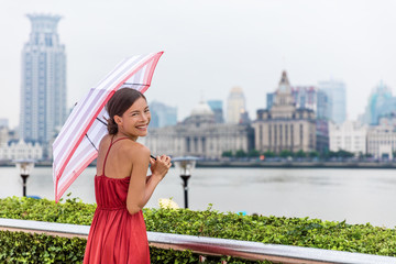 Chinese umbrella woman in rain. Urban landscape panorama of Shanghai city Bund, Pudong Huangpu district, rainy summer day. Tourist traveling in Shanghai, China, Asia travel.