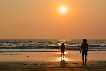 A man and a woman on the shore of the Arabian sea at sunset on the beach in Northern Goa.India