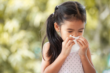 Sick asian little child girl wiping and cleaning nose with tissue on her hand