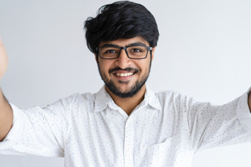 Smiling young man taking selfie photo on gadget which is out of view. Handsome guy looking at camera. Selfie concept. Isolated front view on white background.