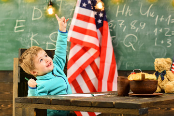 School kid at lesson in 4th of july. Happy independence day of the usa. Little boy in classroom with American flag at knowledge day. Back to school or home schooling. Patriotism and freedom